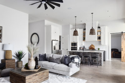living and kitchen area wood tile floor white trim white walls modern light fixtures brick fireplace